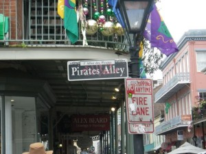 Pirates Alley sign with Mardi Gras decorations above.