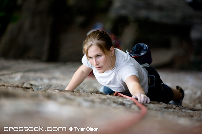 A female climber on a steep rock face looking ...